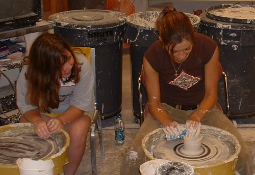 iu east student demonstrates ceramics to a girl