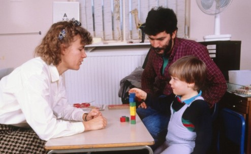 MODEL RELEASED. Child development: young boy (aged around 3-4 years) undertaking an intelligence test to estimate his reasoning skills. He is being asked to arrange the coloured blocks in accordance with instructions given by his assessor (left).
